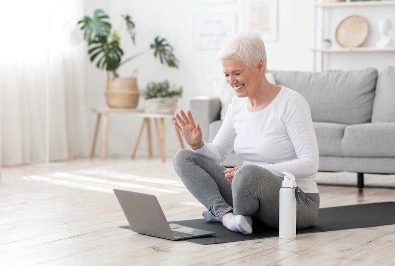 smiling-senior-woman-training-at-home-online-via-l-ZYQTR76
